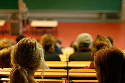 Es sind zwei Studentinnen in einem Hörsaal zu sehen